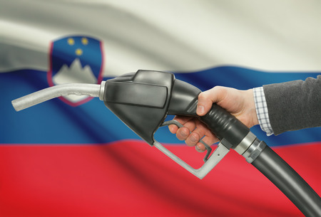 methanol: Fuel pump nozzle in hand with flag on background - Slovenia