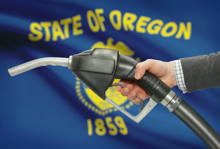 methanol: Fuel pump nozzle in hand with US states flags on background - Oregon