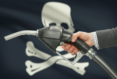 petrochemistry: Fuel pump nozzle in hand with flags on background series - Jolly Roger - symbol of piracy