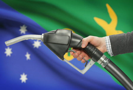 methanol: Fuel pump nozzle in hand with flag on background - Christmas Island Stock Photo