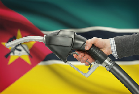 petrochemistry: Fuel pump nozzle in hand with flag on background - Mozambique