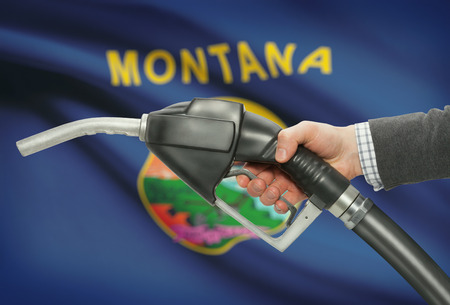 petrochemistry: Fuel pump nozzle in hand with US states flags on background - Montana Stock Photo