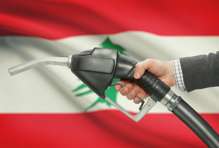 methanol: Fuel pump nozzle in hand with flag on background - Lebanon Stock Photo