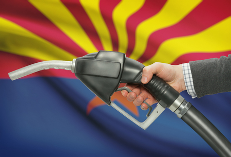 petrochemistry: Fuel pump nozzle in hand with US states flags on background - Arizona