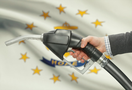 methanol: Fuel pump nozzle in hand with US states flags on background - Rhode Island