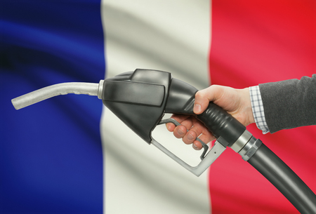 petrochemistry: Fuel pump nozzle in hand with flag on background - France