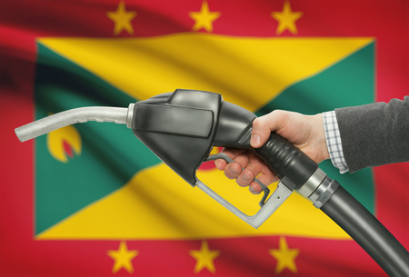 petrochemistry: Fuel pump nozzle in hand with flag on background - Grenada