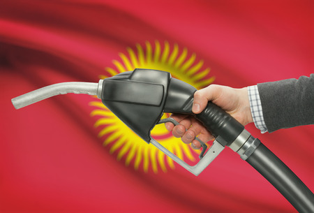 petrochemistry: Fuel pump nozzle in hand with flag on background - Kyrgyzstan Stock Photo