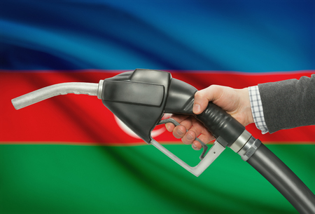 methanol: Fuel pump nozzle in hand with flag on background - Azerbaijan Stock Photo
