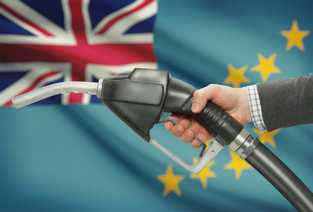petrochemistry: Fuel pump nozzle in hand with flag on background - Tuvalu Stock Photo