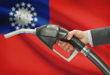 petrochemistry: Fuel pump nozzle in hand with flag on background - Burma