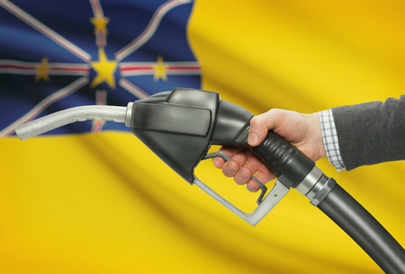 niue: Fuel pump nozzle in hand with flag on background - Niue