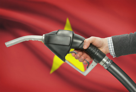petrochemistry: Fuel pump nozzle in hand with flag on background - Vietnam Stock Photo