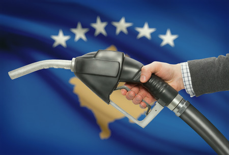 Fuel pump nozzle in hand with flag on background - Kosovo