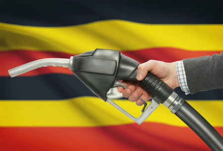petrochemistry: Fuel pump nozzle in hand with flag on background - Uganda