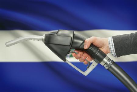 methanol: Fuel pump nozzle in hand with flag on background - El Salvador