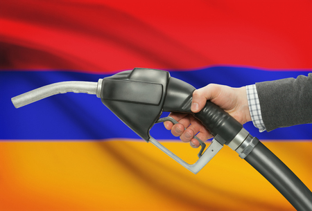 petrochemistry: Fuel pump nozzle in hand with flag on background - Armenia