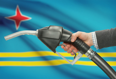 petrochemistry: Fuel pump nozzle in hand with flag on background - Aruba