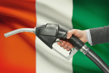 petrochemistry: Fuel pump nozzle in hand with flag on background - Ivory Coast Stock Photo