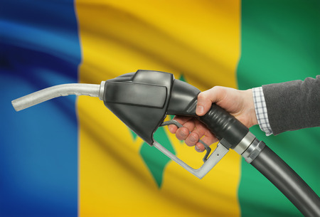 petrochemistry: Fuel pump nozzle in hand with flag on background - Saint Vincent and the Grenadines