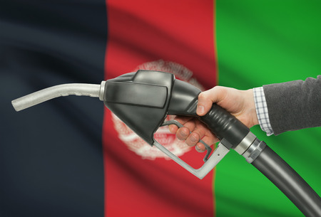 petrochemistry: Fuel pump nozzle in hand with flag on background - Afghanistan Stock Photo