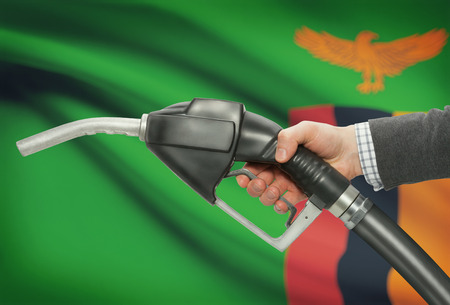 zambian flag: Fuel pump nozzle in hand with flag on background - Zambia