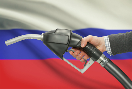 petrochemistry: Fuel pump nozzle in hand with flag on background - Russia Stock Photo