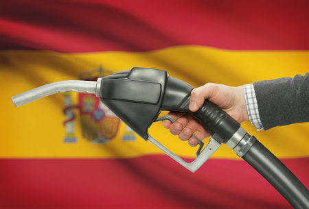 methanol: Fuel pump nozzle in hand with flag on background - Spain