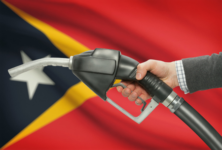 petrochemistry: Fuel pump nozzle in hand with flag on background - East Timor
