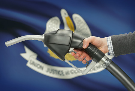 methanol: Fuel pump nozzle in hand with US states flags on background - Louisiana