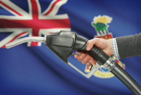 petrochemistry: Fuel pump nozzle in hand with flag on background - Cayman Islands Stock Photo