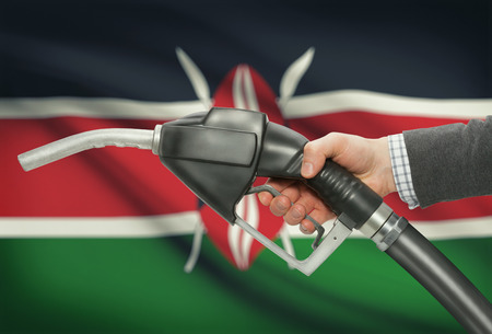 petrochemistry: Fuel pump nozzle in hand with flag on background - Kenya Stock Photo