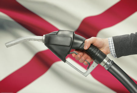 petrochemistry: Fuel pump nozzle in hand with US states flags on background - Alabama Stock Photo