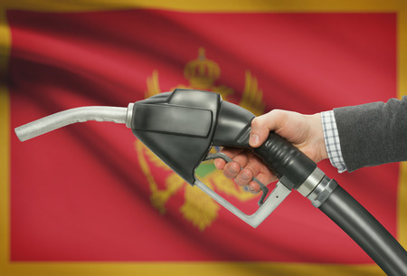 Fuel pump nozzle in hand with flag on background - Montenegro Stock Photo