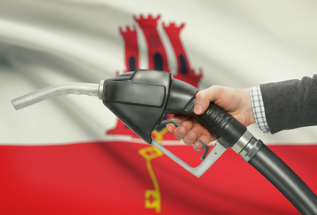 petrochemistry: Fuel pump nozzle in hand with flag on background - Gibraltar