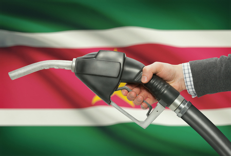 methanol: Fuel pump nozzle in hand with flag on background - Suriname