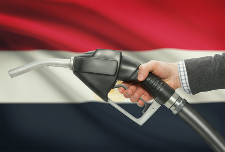 petrochemistry: Fuel pump nozzle in hand with flag on background - Egypt