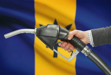 barbadian: Fuel pump nozzle in hand with flag on background - Barbados Stock Photo