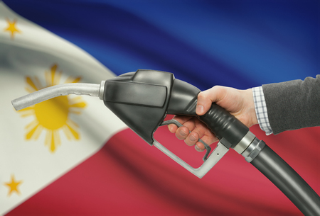 petrochemistry: Fuel pump nozzle in hand with flag on background - Philippines