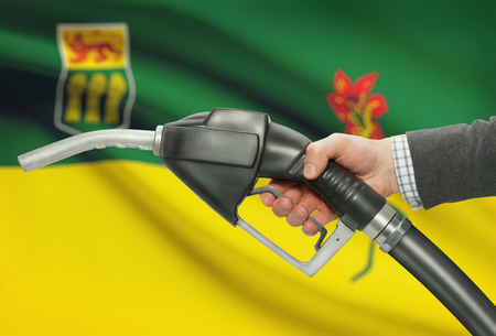 saskatchewan flag: Fuel pump nozzle in hand with Canadian territories and provinces flags on background - Saskatchewan
