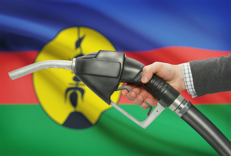 methanol: Fuel pump nozzle in hand with flag on background - New Caledonia