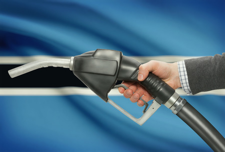 botswanan: Fuel pump nozzle in hand with flag on background - Botswana Stock Photo