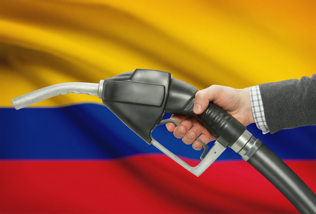 Fuel pump nozzle in hand with flag on background - Colombia
