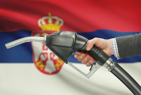 petrochemistry: Fuel pump nozzle in hand with flag on background - Serbia