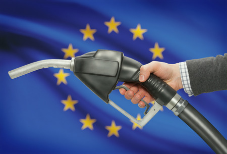petrochemistry: Fuel pump nozzle in hand with flag on background - European Union - EU