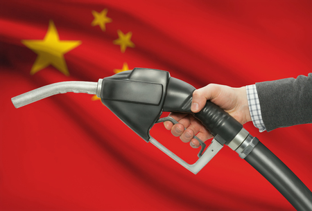 petrochemistry: Fuel pump nozzle in hand with flag on background - China Stock Photo