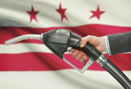 district columbia: Fuel pump nozzle in hand with US states flags on background - District of Columbia