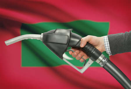 petrochemistry: Fuel pump nozzle in hand with flag on background - Maldives Stock Photo