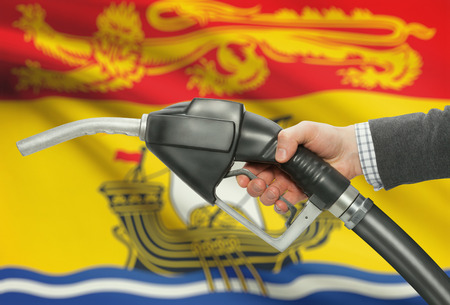 methanol: Fuel pump nozzle in hand with Canadian territories and provinces flags on background - New Brunswick