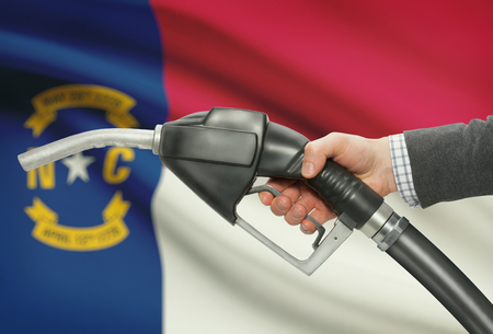 petrochemistry: Fuel pump nozzle in hand with US states flags on background - North Carolina Stock Photo